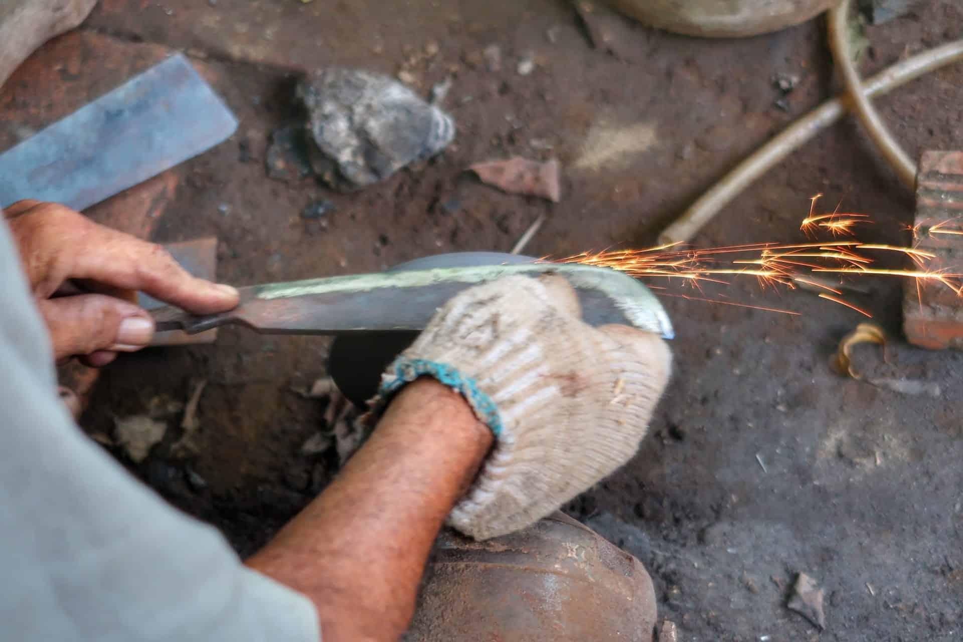 Mand sliber knive af gammelt jern